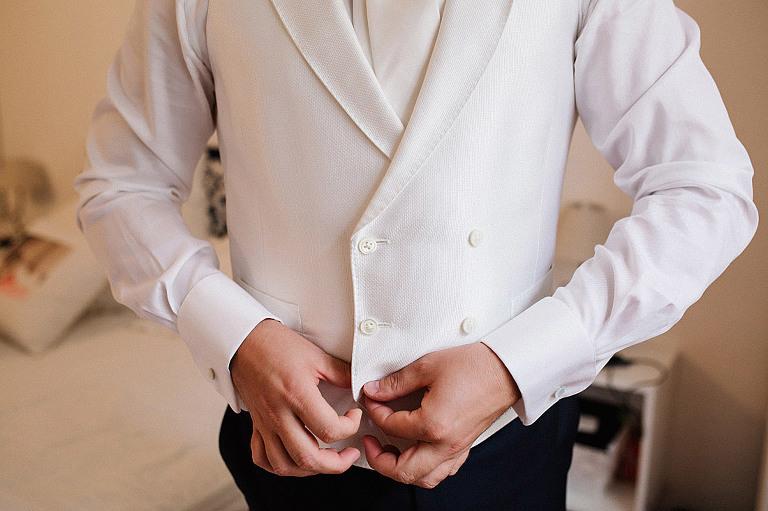 lo sposo si abbottona il gilet